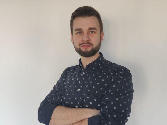 Zdjęcie portretowe: Kamil Kupiński w niebieskiej koszuli w kropki na tle jasnej ściany.