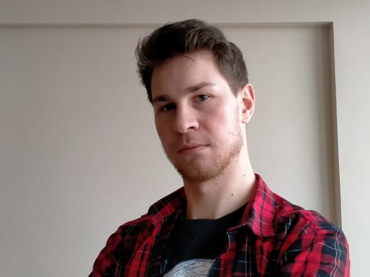 Zdjęcie portretowe: Tomasz Kaczmarek w kraciastej koszuli na tle białej ściany.