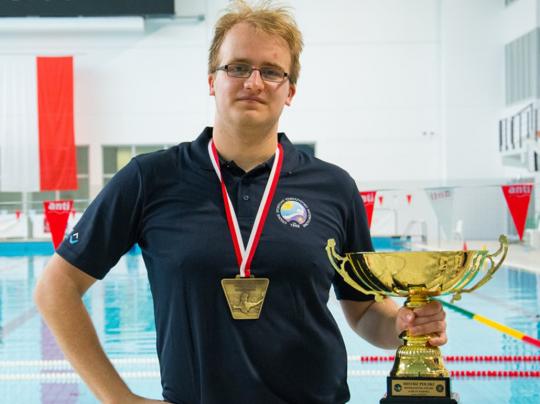 Adrian Wulkiewicz w niebieskiej polówce trzyma złoty puchar, a na szyi ma złoty medal. W tle basen.